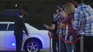 African-American famous woman walking out of limousine and giving autograph to fan on red carpet of celebrity event