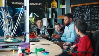 African-american man conducting class with group of kids having club and discussing robotics and technologies. Static 4K shot on Red cinema camera.