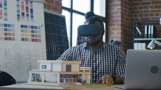 African-American man wearing VR goggles and building three-dimensional model of futuristic house working in office