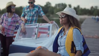 African American woman in life vest holding beer and looking at camera on background of boat and people having fun