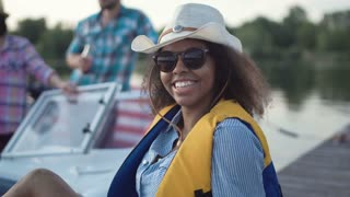 African American woman in life vest looking at camera on background of boat and people having fun