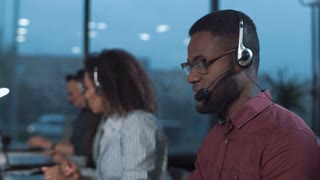 African man with headset working with laptop in support online service and looking at camera