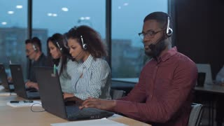 African man with headset working with laptop with other people on the background