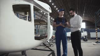 Aircraft mechanic and draftsman standing near plane carcass and talking with each other using digital tablet