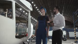 Aircraft mechanic and draftsman standing near plane carcass and talking with each other