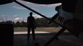 Aircraft mechanic standing in hangar near plane and look into distance