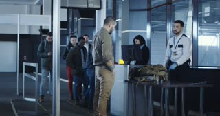 Airport security apprehending a suspect or passenger with men in military uniform pointing a weapon at a kneeling man with his hands on his head at the check-in gate for departures.