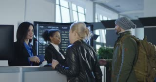Airport security personnel processing passengers at a check-in counter in a departures or arrivals hall checking their identity against passports and thumb prints. 4K shot on Red cinema camera.