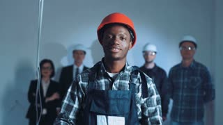 An African builder putting on the protective glasses and headphones and red hard hat. On background builders and manager team