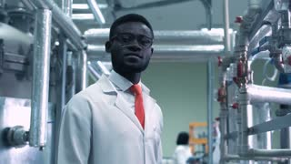 An African scientist looking at camera standing in a plant. Horizontal indoors shot