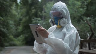 Anonymous biologist in environmental suit browsing tablet in woods