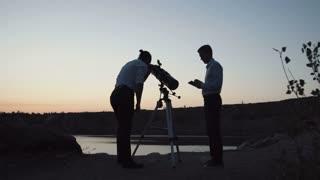 Anonymous man posing on shore of lake using telescope and watching stars