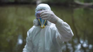 Anonymous person wearing protective suit holding test tube with liquid