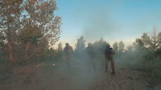 Anonymous soldiers walking in smoke and fire holding guns and shooting