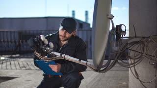 Assembler sitting on roftop and setting satellite dish