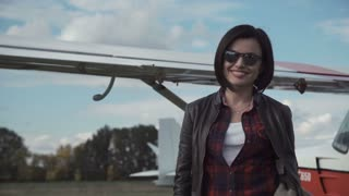 Attractive friendly woman in front of a small fixed wing single engine private plane at an airfield or airport