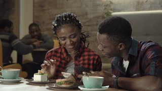 Attractive young black couple in a cafeteria enjoying cups of coffee together and reading a text message on their mobile phone in a close up view.