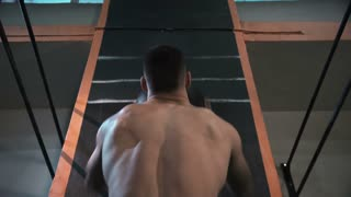 Back view of athletic shirtless man training with heavy weight ball in gym.