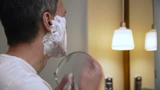 Back view of casual man shaving beard looking at reflection in mirror standing in bathroom.