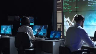 Back view of man and woman in space flight control center. Docking of space modules. Elements of this image furnished by NASA