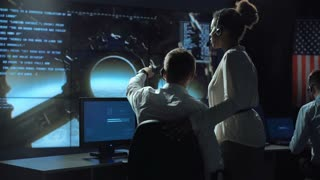 Back view of man pointing and showing to woman in space flight control center. Moon landing of spaceship module