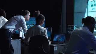 Back view of people sitting and working at computers in space mission control center