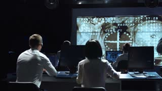 Back view of people working and managing flight in mission control center. Docking to the international space station in space then celebrate. Elements of this image furnished by NASA