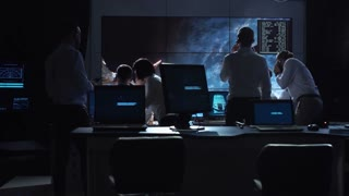 Back view of people working and managing flight in mission control center. Elements of this image furnished by NASA
