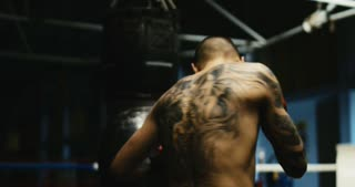 Back view of shirtless man with tattoo on back punching bag while practicing Thai box in gym.