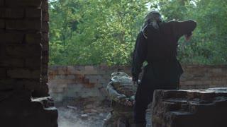 Back view of terrorist murdering soldier hostage in ruins of building