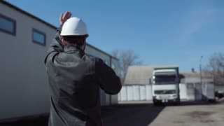 Back view of the manager leading the truck arrival to the warehouse