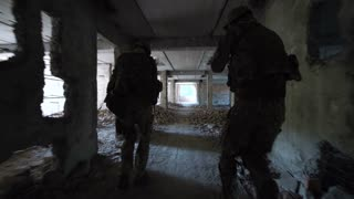 Back view of two men of swat exploring abandoned and ruined building