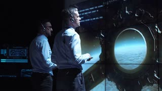 Back view of two supervisors standing at screen in space center and controlling landing on Moon
