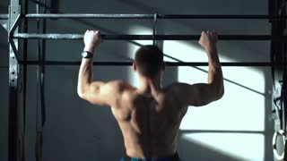 Back view of unrecognizable sportsman without shirt doing chin-ups hanging on bar in sunny gym.