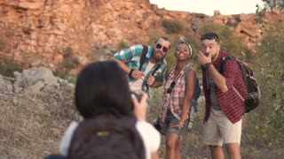 Back view of woman with backpack using photo camera and photographing friends while traveling