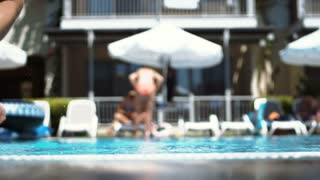 Back view of young boy jumping to swimming pool in hotel