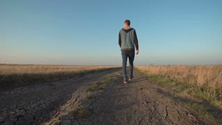 Back view of young lone man walking away down a rural road in a low angle view in a conceptual motion clip