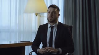 Bearded businessman sitting in chair inside of hotel room and preparing speech with keynotes.
