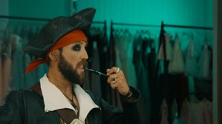 Bearded man in costume of pirate rehearsing facial expressions in front of mirror before performance or before shooting a movie