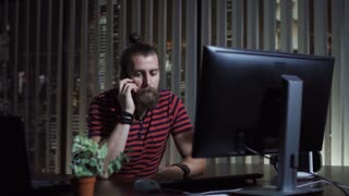 Bearded man sitting at computer and talking on phone in the office at night