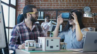 Bearded man working with young Korean girl helping with VR goggles and creating modern house project