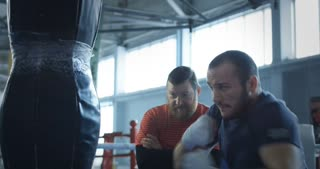 Bearded trainer watching sportsman punching bag and training boxing attacks.