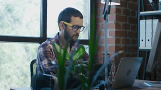 Bearded young man in glasses concentrated on work while using computer in office