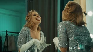 Beautiful blond woman in gorgeous sparkling dress and gloves standing in front of mirror in dressing room preparing for show