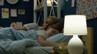 Beautiful woman getting little girl to bed and comforting with love before going to sleep and lying near
