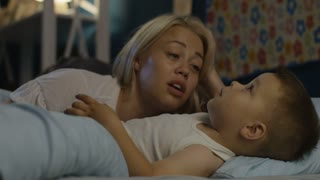 Beautiful woman lying with little boy in bed and telling interesting story before going to sleep at night