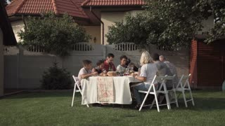 Big family sitting and having dinner together at table in the garden