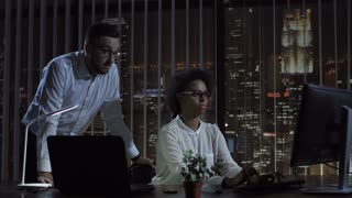 Black and white woman and man working together at computer in office at night