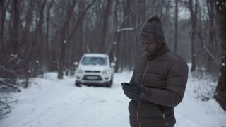Black man in winter jacket talking on smartphone standing on remote winter road with broken car.