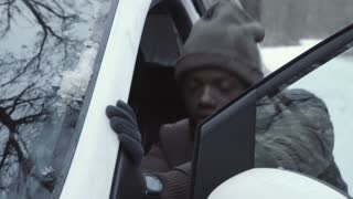 Black man in winter outfit pushing car trying to fire up engine on snowy remote road.
